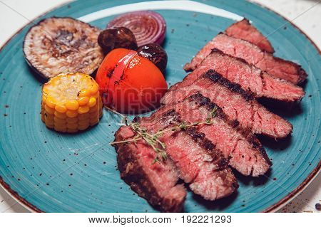 Pieces of beef and vegetables cooked on the grill.