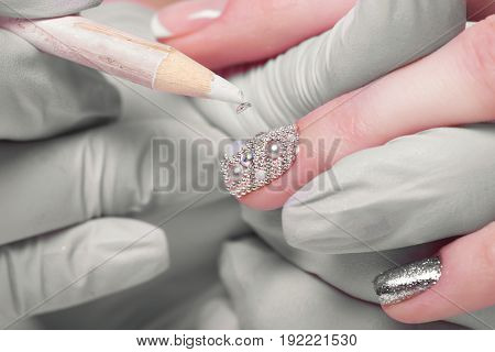 Closeup finger nail care by manicure specialist in beauty salon. Manicurist Glues rhinestones on nails