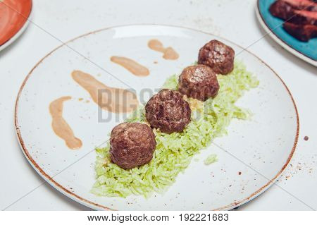 Meat balls in sauce with boiled rice. Food photo.