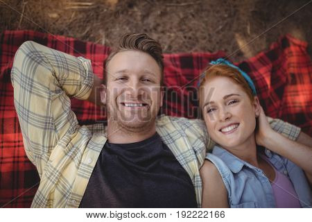 Overhead view of happy young couple resting on mat at farm
