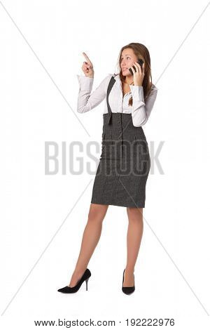 The young woman talks by a mobile phone and shows on an imaginery object over white background.