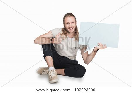 Sitting Blond Man Holding Empty Speech Bubble And Showing Thumb Up, Isolated On White
