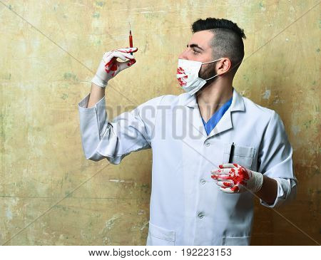 Syringe With Blood In Hand Of Doctor In Procedure Mask
