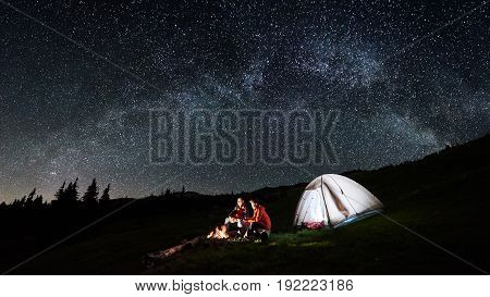 Night Camping In The Mountains. Couple Tourists Have A Rest At A Campfire Near Illuminated Tent Unde