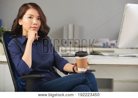 Portrait of serious Asian businesswoman posing with her hand on chin and paper coffee cup in another hand