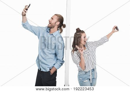 Excited Young Couple Taking Selfie With Smartphones While Standing Separated By Wall