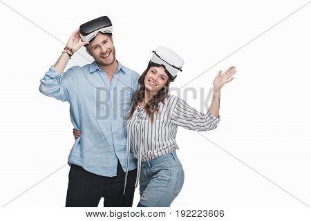 Happy Young Couple In Virtual Reality Headsets Standing Embracing And Smiling At Camera