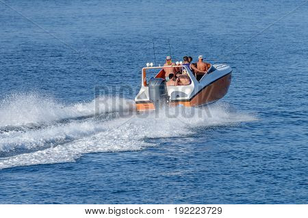 image of people ride a motor boat in the sea