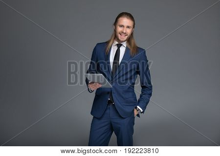 Young Smiling Businessman In Suit Holding Digital Tablet And Looking At Camera