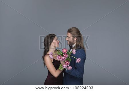 Young Sweethearts In Evening Outfit Holding Bouquet Of Peonies And Looking On Each Other