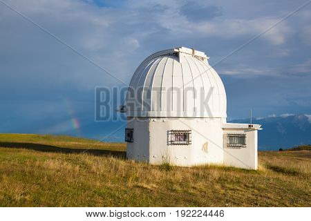 Rainbow and observatory dome in the Gerlitzen Apls in Austria.View of the mountains in Slovenia.