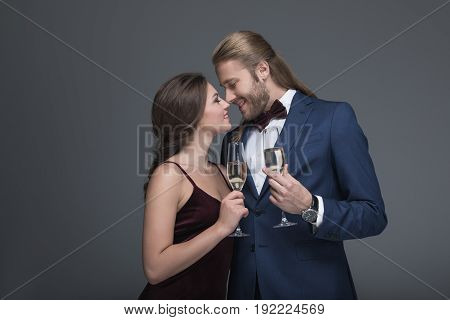 Young Couple In Evening Fashion Outfit Able To Kiss While Holding Glasses With Champagne