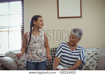Grandmother and granddaughter having fun in living room at home