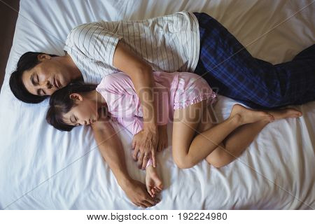 Father and daughter sleeping together in bedroom at home