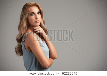 Waist-up portrait of attractive young blonde posing against grey background, copy space to the right