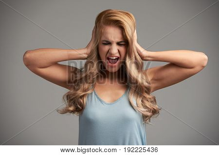 Portrait of young woman shouting with her eyes closed and covering her ears with hands