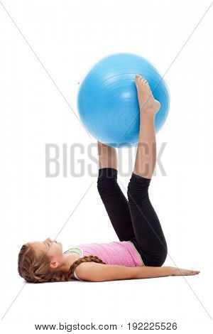 Young girl doing legs and abdomen gymnastic exercises using a large rubber ball - isolated