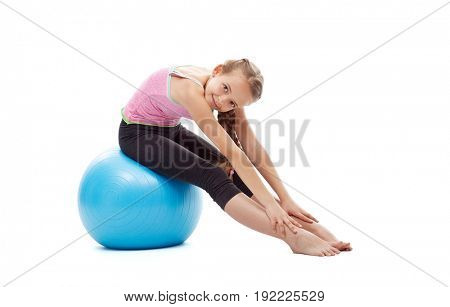 Happy young girl doing stretching gymnastic exercise sitting on a large rubber ball - isolated