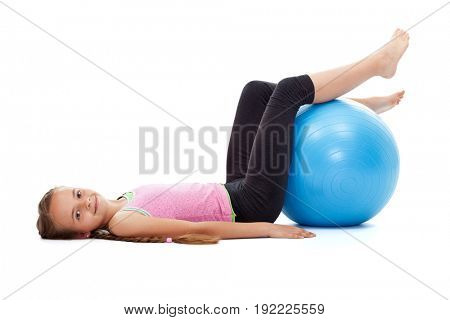 Happy young girl exercising with large gymnastic rubber ball - lying on the floor smiling, isolated