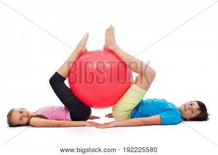 Young boy and girl exercising with a large gymnastic rubber ball - lying on the floor