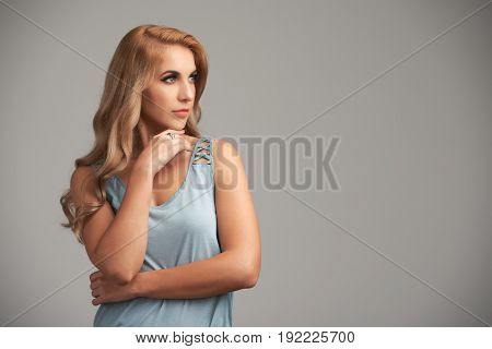 Beautiful blonde woman looking away with her hand on chin, copy space to the righ