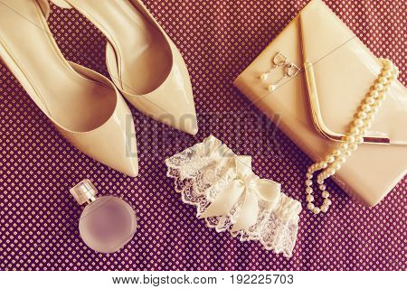 Bride's shoes garter perfume necklace earrings and clutch are on burgundy cloth surface