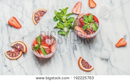 Blood orange and strawberry summer Sangria. Fruit refreshing rose wine cocktails in glasses with ice and mint over grey marble background, top view, horizontal composition