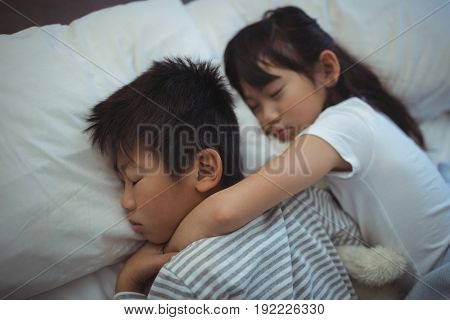 Siblings sleeping on the bed in bed the room at home