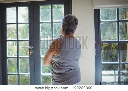 Thoughtful senior woman looking through window in bed room at home