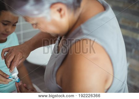 Grandmother applying toothpaste on granddaughters brush in the bathroom at home