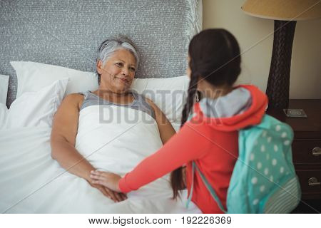 Granddaughter comforting sick grandmother in bed room at home