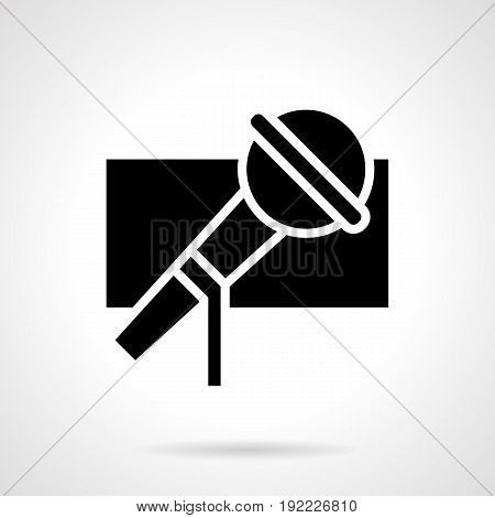 Abstract monochrome symbol of microphone. Music show, singing festival and vocal party. Symbolic black glyph style vector icon.