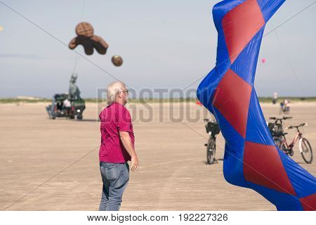 FANOE DENMARK JUNE 17 2017: Kite Flyer fights with his kite on big Fanoe beach. (Series 1 of 4) Fanoe Kite Fliers Meeting June 2017.