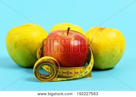 Several Yellow And Red Apples With Rolled Yellow Flexible Ruler