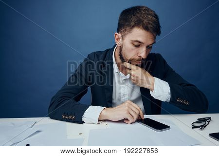 Business man, business man looking into the phone, man on a blue background, business man at the desk