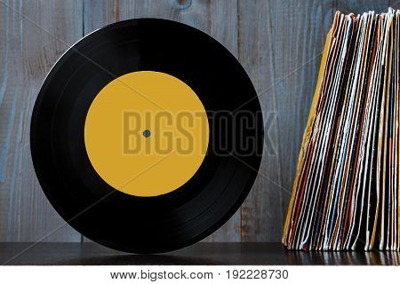 Old vinyl plate and a stack of discs against a wooden wall background.