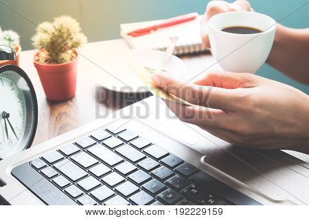 Happy woman drinking hot coffee and holding credit card Online shopping concept
