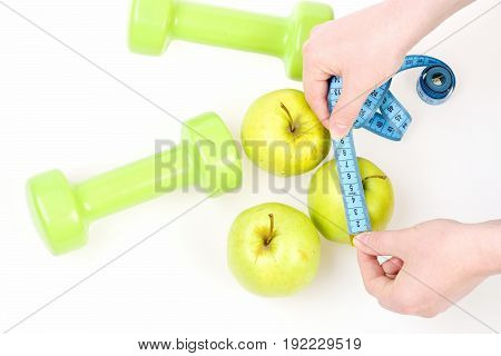 Hands Measure Apple Size With Cyan Measuring Tape