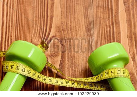 Dumbbells Of Green Colour Tied With Yellow Flexible Ruler