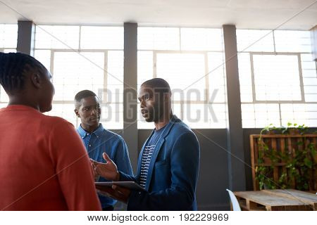 Three focused young African business colleagues deep in conversation together while standing in a large modern office