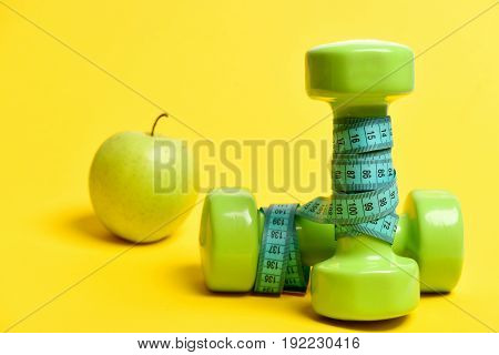 Dumbbells Tied With Turquoise Flexible Ruler And Green Apple