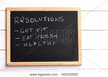 Blackboard with written checklist of resolutions: get fit eat fresh healthy. Vintage wooden background copy space