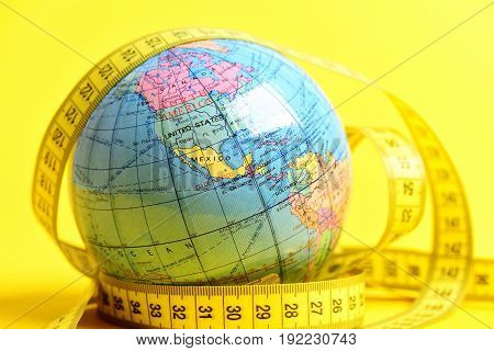 globe with centimeter on yellow background. Diet and health in world concept