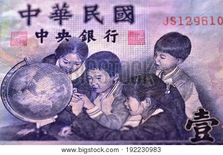 Enlarged view on a portion of a 1000 Taiwan dollar bill showing Chinese characters and four school children who are looking at a globe