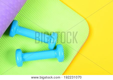 Dumbbells In Blue Colour On Green And Purple Yoga Mat