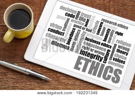 ethics and moral dilemma word cloud on a  digital tablet with a cup of coffee