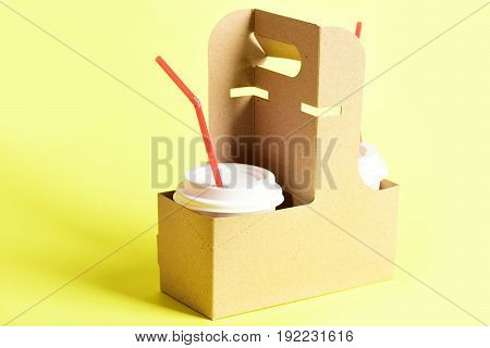Takeaway food concept with pair of plastic cups covered with lids and holding straws placed in cardboard packages light yellow background