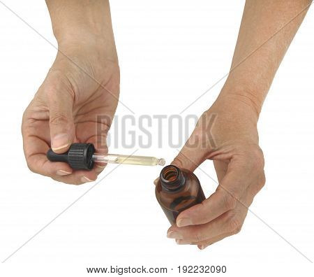 Holding an Essential Oils Dropper Bottle - female hands holding an open dropper bottle with essential oils isolated on a white background