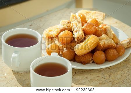 plate with variation of oriental delicious sweets and two cup of black tea on marble table