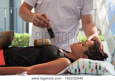 A professional masseur performs chakra stimulation with Tibetan bells